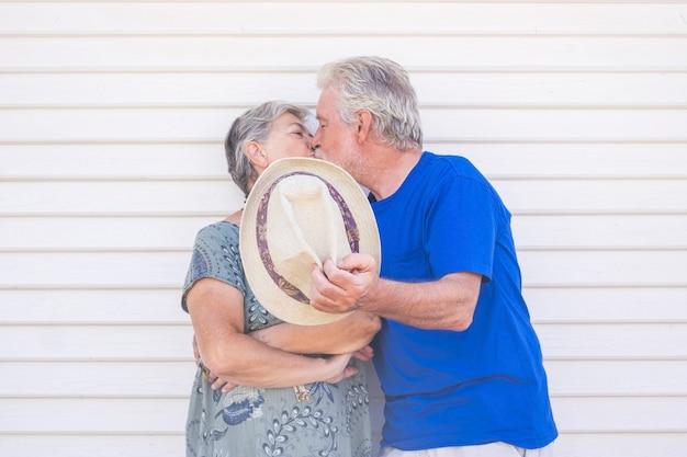Concepto del día de san valentín con ancianos hermosa pareja senior besándose con un sombrero beige con una pared de madera blanca detrás de ellos.