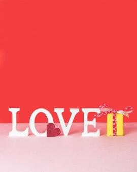 Concepto de día de san valentín con cartas de amor blancas, un corazón rojo y una caja de regalo amarilla sobre fondo rosa y rojo. imagen vertical con espacio para copiar texto