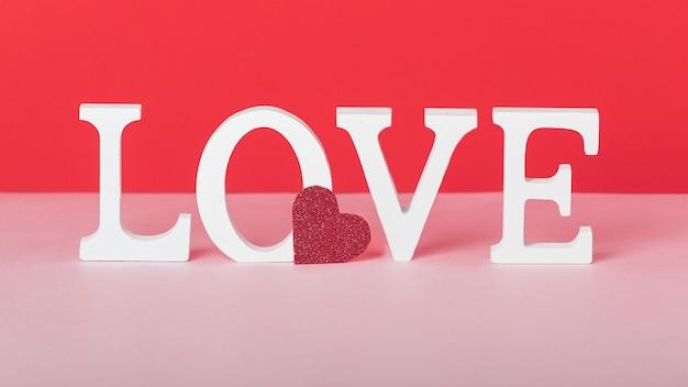 Concepto del día de san valentín con cartas de amor blancas y un corazón rojo sobre fondo rosa y rojo