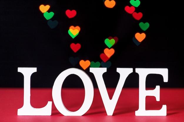 Concepto de día de san valentín con cartas de amor blancas sobre un fondo negro con luces de colores en forma de corazón