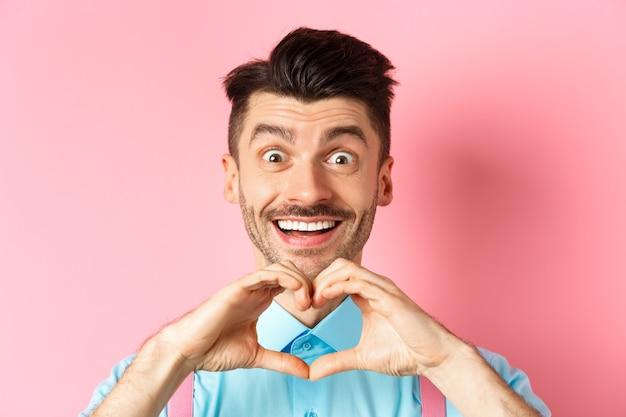 Concepto de día de san valentín cerca de chico romántico que parece feliz sonriendo y mostrando gesto de corazón stan ...