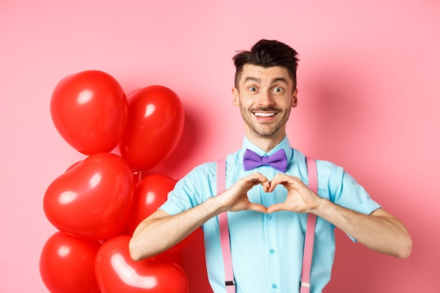 Concepto de día de san valentín chico romántico en pajarita mostrando gesto de corazón y decir te amo con esperanza ...