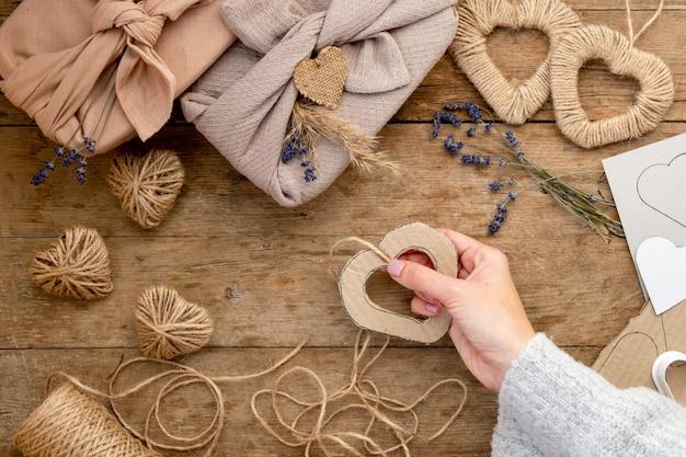 Concepto de día de san valentín de desperdicio cero y maqueta. empaquetado de regalo estilo furoshiki con lavanda, yute de hierba de pampa y corazones de estarcido. vista superior o endecha plana. instrucción, paso a paso
