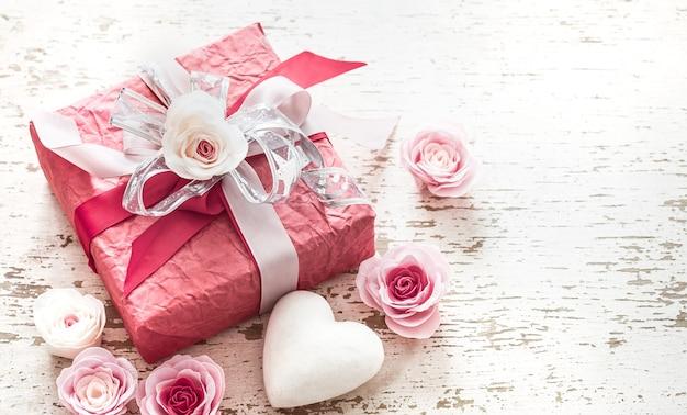 Concepto de día de san valentín y día de la madre, caja de regalo roja con lazo y rosas sobre fondo de madera clara