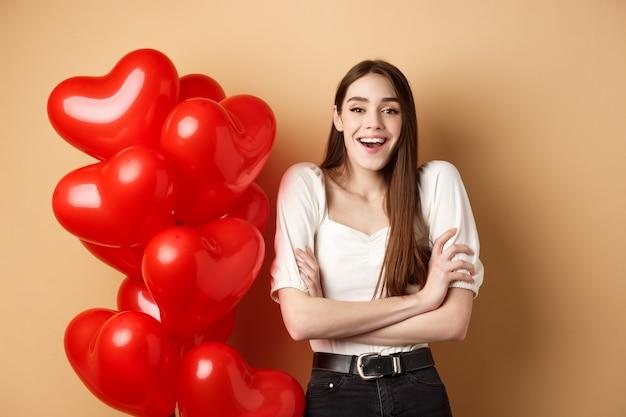 Concepto de día de san valentín hermosa mujer joven divirtiéndose riendo y sonriendo a la cámara de pie cerca ...