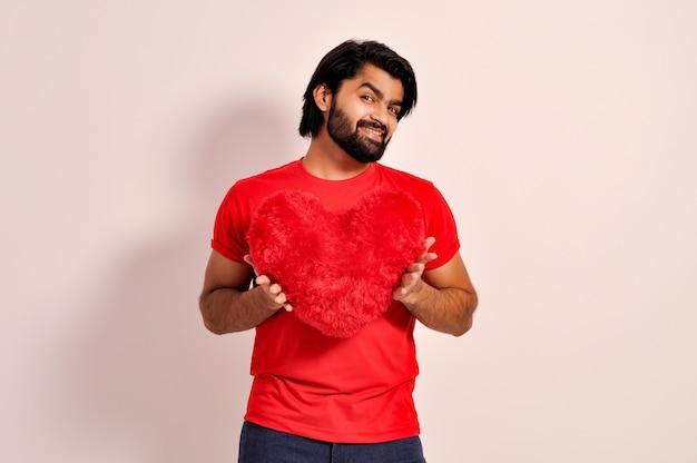Concepto de día de san valentín hombre indio guapo joven sosteniendo una almohada en forma de corazón rojo en el amor