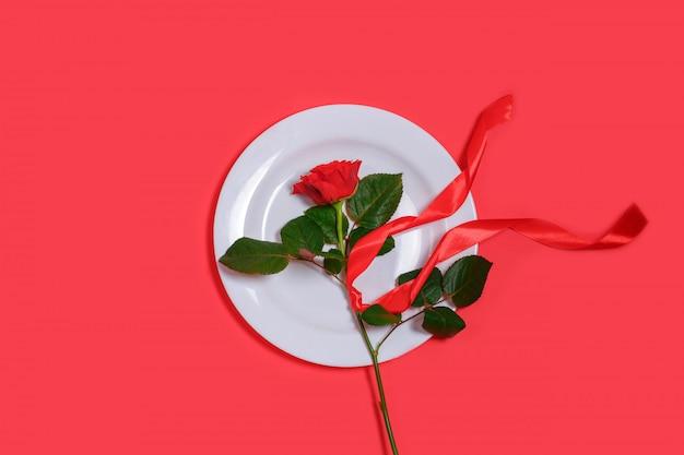 Concepto del día de san valentín con rosa roja y cinta en plato blanco sobre fondo rojo.