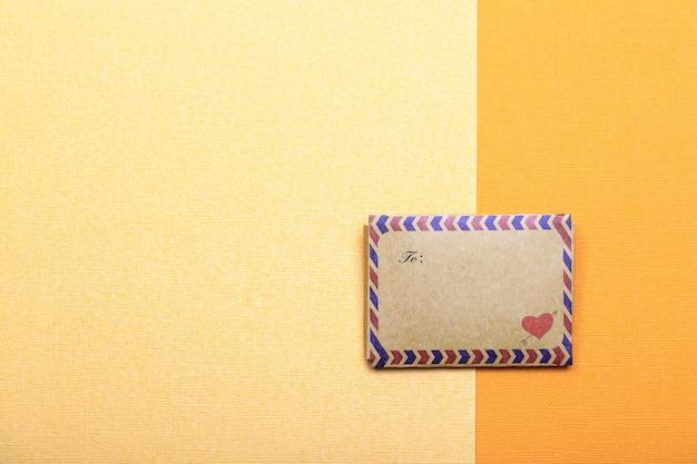 Concepto de día de san valentín con sobre con corazón sobre papel amarillo
