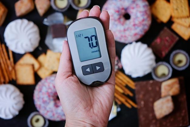 Concepto de diabetes: dulces y alimentos poco saludables con glucómetro en mano. nutrición causa enfermedad diabética