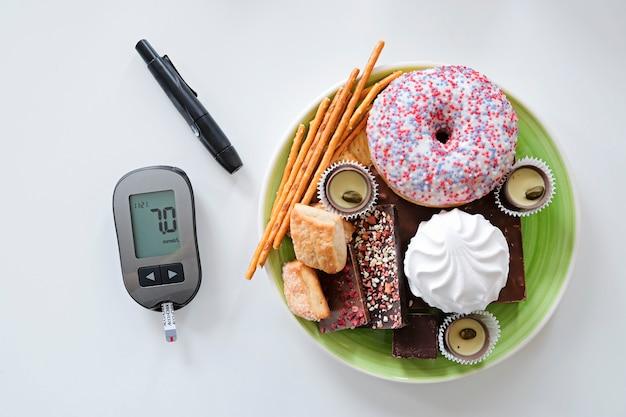 Concepto de diabetes dulces y alimentos poco saludables con glucómetro.