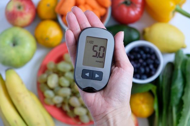 Concepto de diabetes: glucómetro en mano y comida sana.