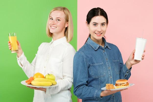 Concepto de dieta. alimentos saludables y útiles. hermosas mujeres jóvenes eligiendo entre frutas y comida rápida poco saludable en el estudio. emociones humanas y conceptos de comparación