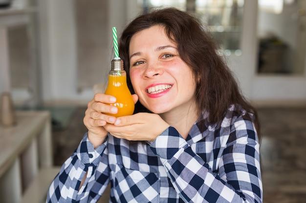 Concepto de dieta y bebidas de vitamina de estilo de vida saludable cerca de mujer feliz bebiendo jugo en casa