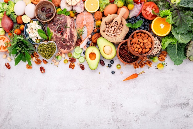 Concepto de dieta cetogénica baja en carbohidratos. ingredientes para la selección de alimentos saludables sobre fondo de hormigón blanco.