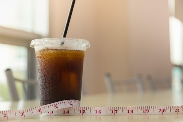 Concepto de dieta y comida. ciérrese para arriba de la taza plástica para llevar de café sólo helado (americano) con la cinta métrica en la tabla en tienda del restaurante con el sapce de la copia.