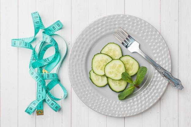 Concepto de dieta diapositivas de pepino fresco en una placa y cinta centímetro en una mesa blanca.