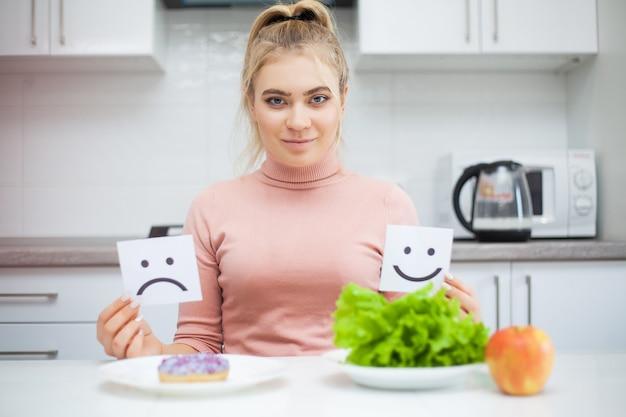 Concepto de dieta, hermosa joven eligiendo entre comida sana y comida chatarra