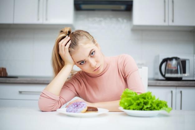 Concepto de dieta, hermosa mujer joven que elige entre comida saludable y comida chatarra