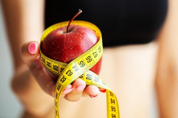 Concepto de dieta. manzana con cinta métrica en mano femenina