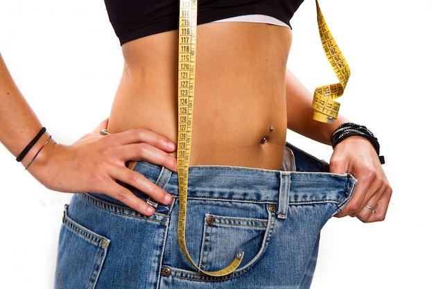 Concepto de dieta: mujer con jeans grandes después de la dieta.