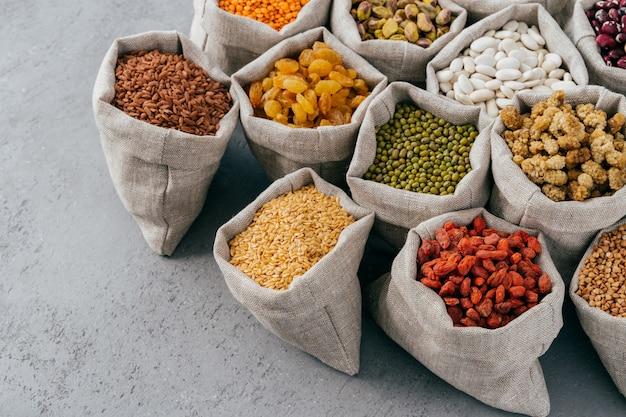 Concepto de dieta, nutrición y alimentación saludable. coloridos cereales y frutos secos ricos en proteínas en sacos de arpillera. semillas de legumbres secas.
