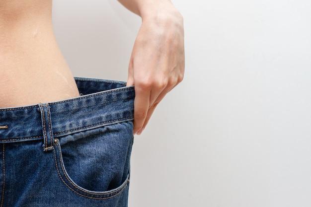 Concepto de dieta y pérdida de peso. mujer en jeans de gran tamaño.