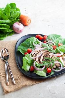 Concepto de dieta y salud. ensalada de pollo a la parrilla servida en plato negro y mesa de concreto
