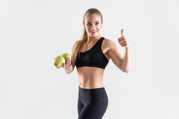Concepto de dieta saludable. mujer de felicidad sosteniendo la manzana y los pulgares para arriba. tiro del estudio