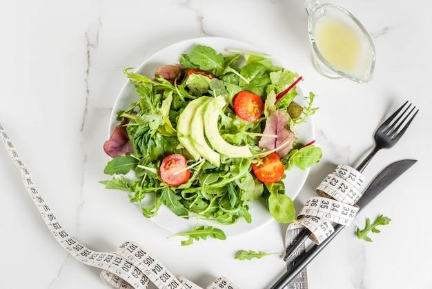 Concepto de dieta saludable, pérdida de peso, conteo de calorías. plato con hojas de ensalada verde, tomate, aguacate con aderezo de yogurt
