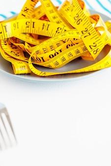 El concepto de la dieta. el tenedor rebobinado centímetro acostado en primer plano de la placa