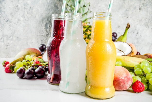 Concepto de diferentes jugos de frutas batidos dieta de vitaminas de verano con frutas tropicales y bayas sobre un fondo claro