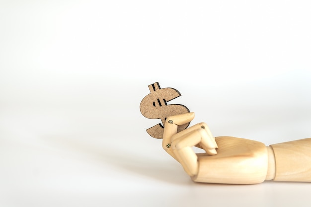 Concepto de dinero empresarial. mano de madera sosteniendo madera signo de dólar estadounidense sobre fondo blanco.