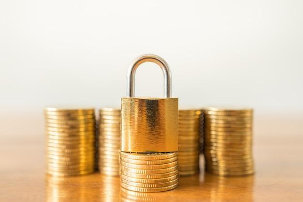 Concepto de dinero, finanzas, jubilación y seguridad. ciérrese para arriba del bloqueo de teclas principal en la pila de monedas de oro en la tabla de madera con el espacio de la copia.