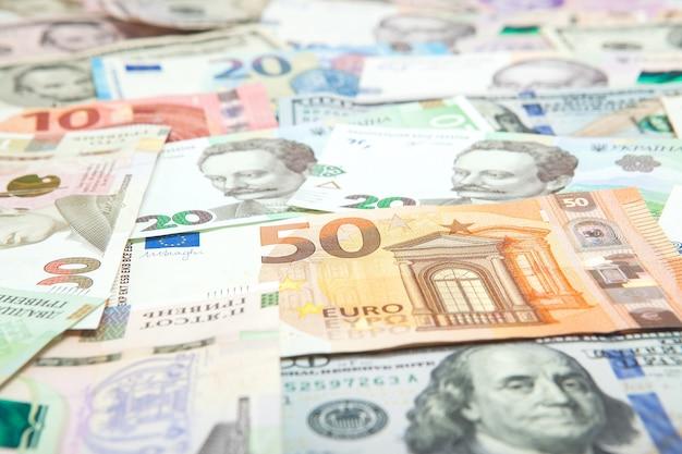 Concepto de dinero y finanzas. nuevo billete de cien dólares sobre fondo abstracto colorido de billetes en moneda nacional ucraniana, estadounidense y euro