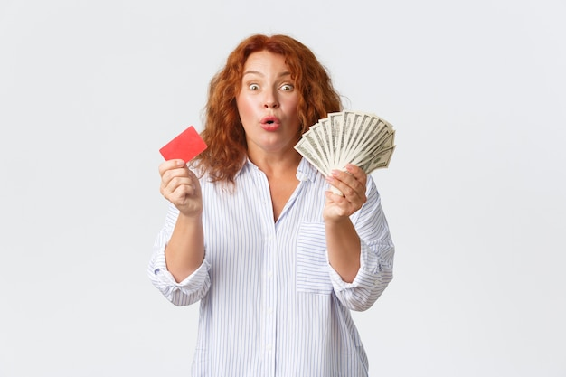 Concepto de dinero, finanzas y personas. mujer pelirroja de mediana edad alegre y emocionada en blusa casual, sosteniendo dinero y tarjeta de crédito con sonrisa optimista, pared blanca de pie.