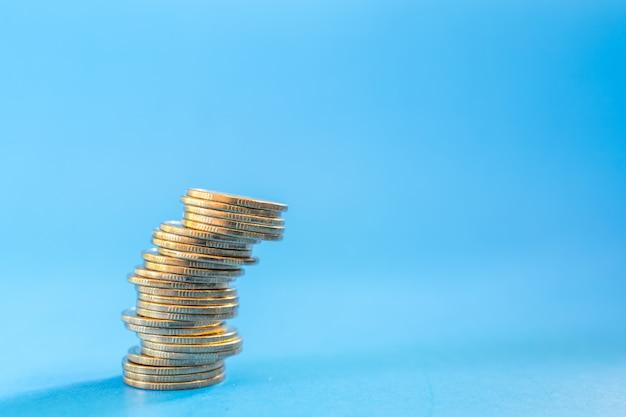 Concepto de dinero, negocios y riesgos. primer de la pila inestable de monedas en fondo azul con el espacio de la copia.