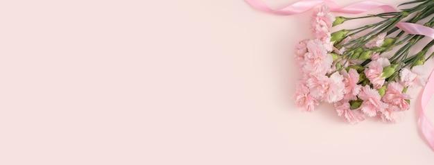 Concepto de diseño de diseño de saludo de vacaciones del día de la madre con ramo de clavel sobre fondo de mesa rosa pastel