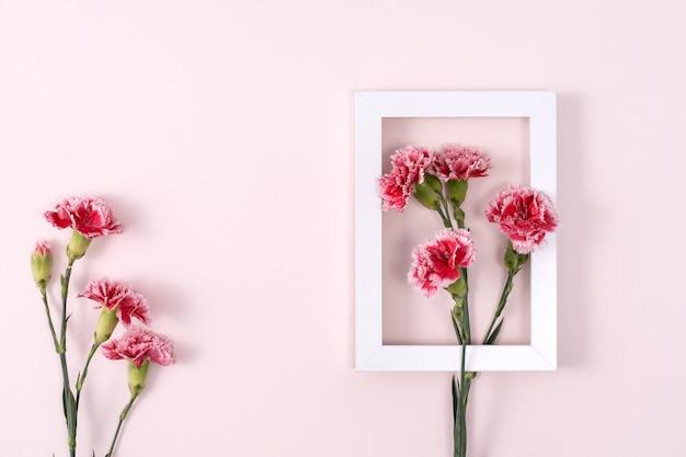Concepto de diseño de fondo de saludo de vacaciones del día de la madre con ramo de claveles sobre fondo rosa