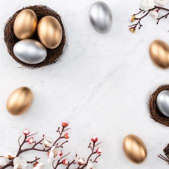 Concepto de diseño de huevos de pascua dorados y plateados en el nido con flor de ciruelo blanco sobre fondo de mesa de mármol blanco brillante.