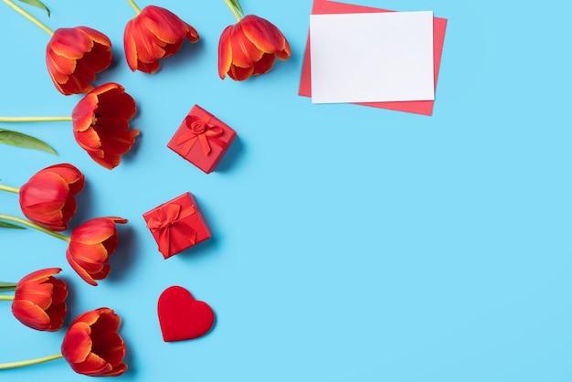 Concepto de diseño de regalo de felicitación navideña del día de la madre con ramo de tulipán rojo y tarjeta sobre fondo de mesa azul brillante