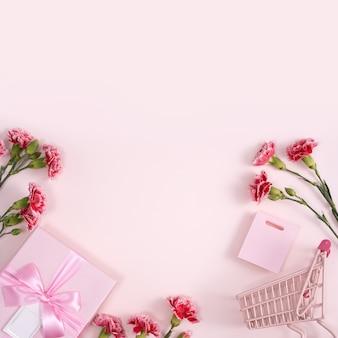 Concepto de diseño de saludo navideño del día de la madre con ramo de clavel y regalo en superficie rosa
