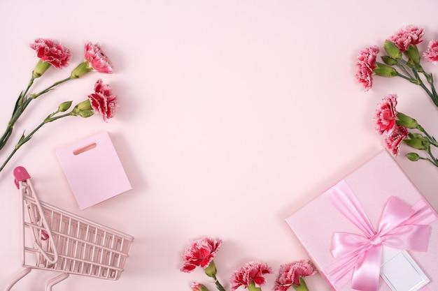 Concepto de diseño de saludo de vacaciones del día de la madre con ramo de clavel y regalo sobre fondo rosa