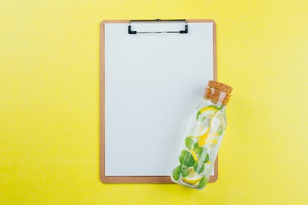 El concepto de diseño del tablero de clip de la maqueta y el agua de la menta de limón en fondo amarillo.
