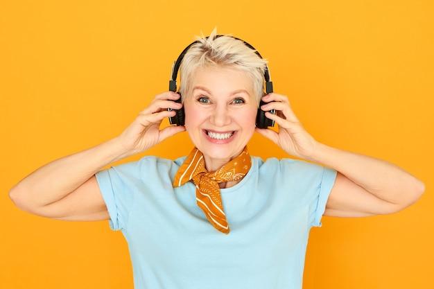 Concepto de dispositivos electrónicos, entretenimiento, jubilación y edad. encantadora mujer rubia feliz jubilado con auriculares inalámbricos negros, disfrutando de un agradable sonido de audio de alta resolución, escuchando música