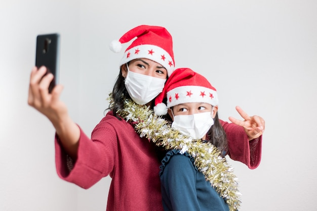 Concepto de distancia social durante el coronavirus navideño. madre e hija latinas toman un selfie con teléfono móvil con mascarilla.