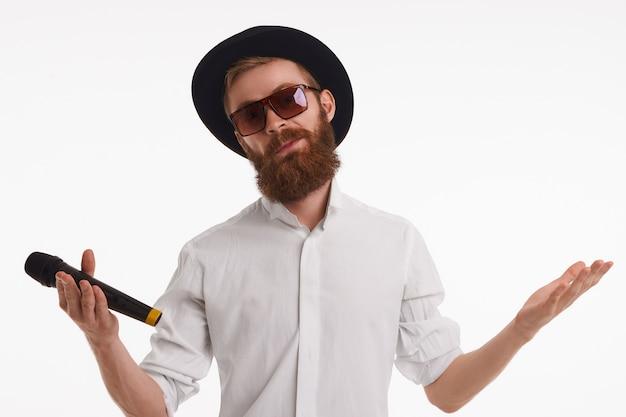 Concepto de diversión, entretenimiento, música, estilo y moda. retrato de carismático sin afeitar con sombrero y sombras con mirada confusa, encogiéndose de hombros, llenando de timidez mientras canta una canción en el bar de karaoke