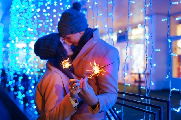 Concepto de diversión de navidad y año nuevo. pareja de enamorados quemando bengalas por iluminación de vacaciones al aire libre. vacaciones festivas