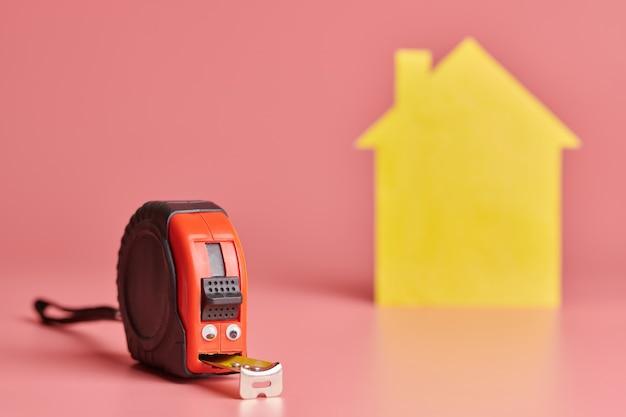 Concepto divertido de cinta métrica de metal. renovación de la casa. reparación de viviendas y concepto redecorado. figura en forma de casa amarilla sobre fondo rosa.