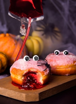 Concepto divertido de la fiesta de halloween. donuts con mermelada en una tabla de madera