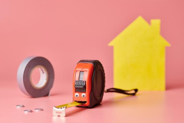 Concepto divertido de renovación de casa. cinta métrica de metal y otros artículos de reparación. reparación del hogar y concepto redecorado. casa amarilla